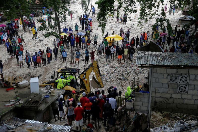 Residents look at workers at an area affected by the passage of Tropical Storm Laura, in Port-au-Prince