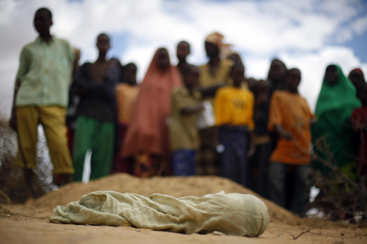 FILE - In this Saturday Aug. 6, 2011 file photo, the shrouded body of 12-month-old Liin Muhumed Surow, who died of malnutrition 25 days after reaching the camp according to her father Mumumed, lies before burial at UNHCR's Ifo Extension camp, near Dadaab in Kenya close to the Somali border. Officials in East Africa say a report to be released this week by two U.S. government-funded famine and food agencies gives the highest death toll yet from Somalia's 2011 famine, estimating that 260,000 people died - more than double previous estimates. (AP Photo/Jerome Delay, File)