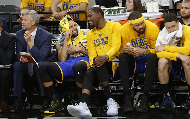 The Warriors' Stephen Curry and Kevin Durant share a laugh in the closing minutes of Game 3 Saturday night. (AP)