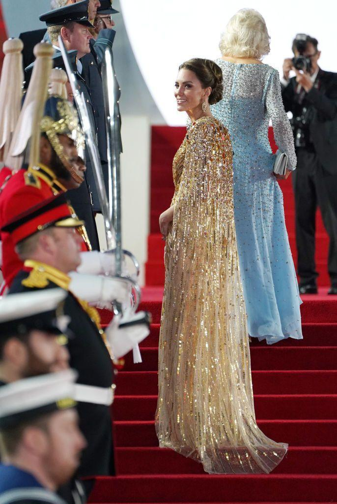 """<p>The Duchess of Cambridge looked just like a Bond girl while attending the <em><a href=""""https://www.townandcountrymag.com/society/tradition/a37710183/kate-middleton-james-bond-premiere-gold-dress-photos/"""" rel=""""nofollow noopener"""" target=""""_blank"""" data-ylk=""""slk:No Time to Die"""" class=""""link rapid-noclick-resp"""">No Time to Die </a></em><a href=""""https://www.townandcountrymag.com/society/tradition/a37710183/kate-middleton-james-bond-premiere-gold-dress-photos/"""" rel=""""nofollow noopener"""" target=""""_blank"""" data-ylk=""""slk:premiere in London"""" class=""""link rapid-noclick-resp"""">premiere in London</a>. Her glimmering, gold cape dress was from designer Jenny Packham. </p>"""