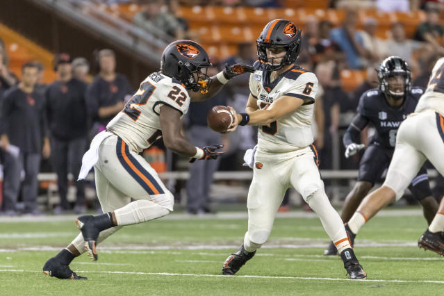 Oregon State quarterback Jake Luton (6) hands off the football to his running back Jermar Jefferson (22) during the first half of an NCAA college football game, Saturday, Sept. 7, 2019, in Honolulu. (AP Photo/Eugene Tanner)