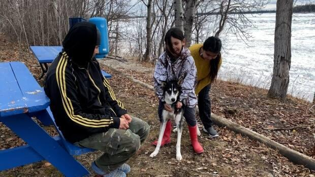 Kierstyn Hope, front, and Shaylyn Hope, back, play with their dog Hunter behind the Snowshoe hotel.