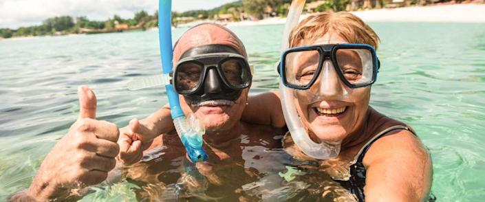 Senior happy couple taking selfie in tropical sea excursion with water camera