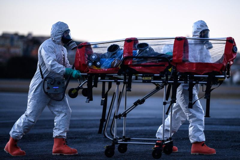 Members of the Military Firefighter Brigade of Minas Gerais (CBMMG) wearing protective gear, demonstrate the use of an isolation stretcher, or bubble stretcher, to transport patients infected with coronavirus (COVID-19), at Pampulha Airport, in Belo Horizonte, state of Minas Gerais, Brazil, on July 22, 2020. - The equipment, which can be used to transport patients in aircrafts and ambulances, filters the air that the patient exhales in addition to isolating him. (Photo by DOUGLAS MAGNO / AFP) (Photo by DOUGLAS MAGNO/AFP via Getty Images)