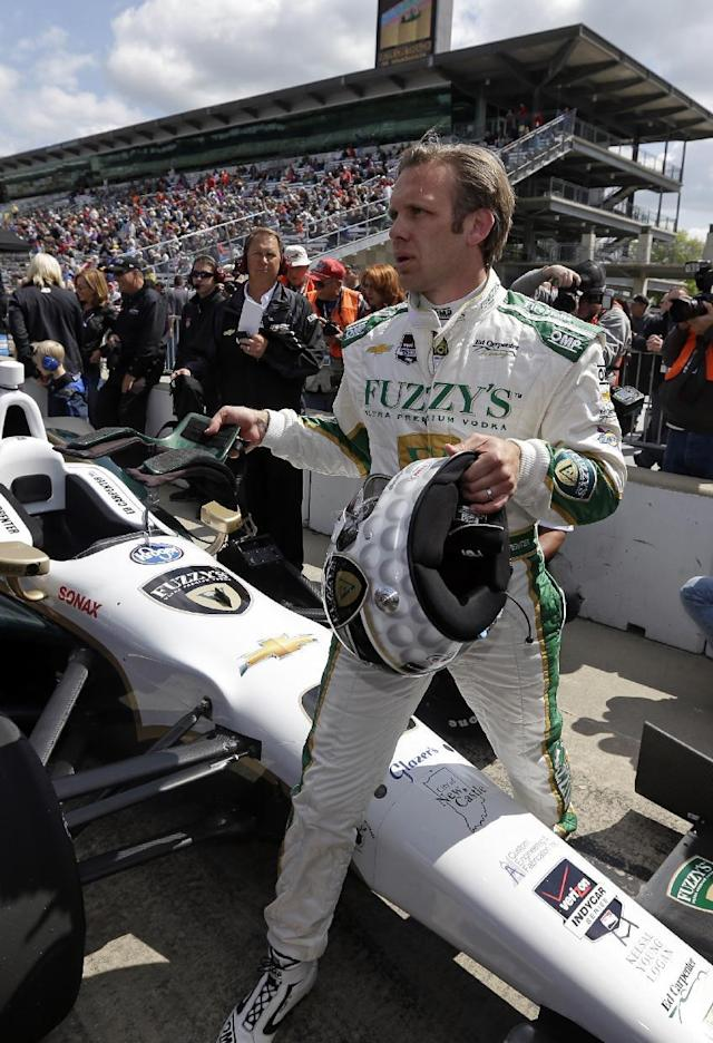 Ed Carpenter steps over his car after he qualified on the first day of qualifications for Indianapolis 500 IndyCar auto race at the Indianapolis Motor Speedway in Indianapolis, Saturday, May 17, 2014. (AP Photo/Darron Cummings)