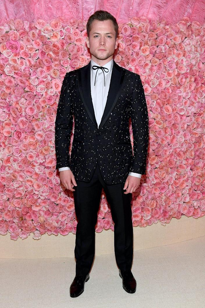 Taron Egerton stands in a black, sparkly tuxedo in front of a wall of pink flowers.
