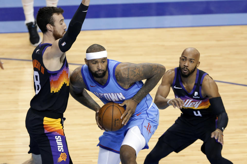 Houston Rockets center DeMarcus Cousins, middle, looks to pass the ball under pressure from Phoenix Suns forward Frank Kaminsky (8) and guard Jevon Carter (4) during the first half of an NBA basketball game Wednesday, Jan. 20, 2021, in Houston. (AP Photo/Michael Wyke)