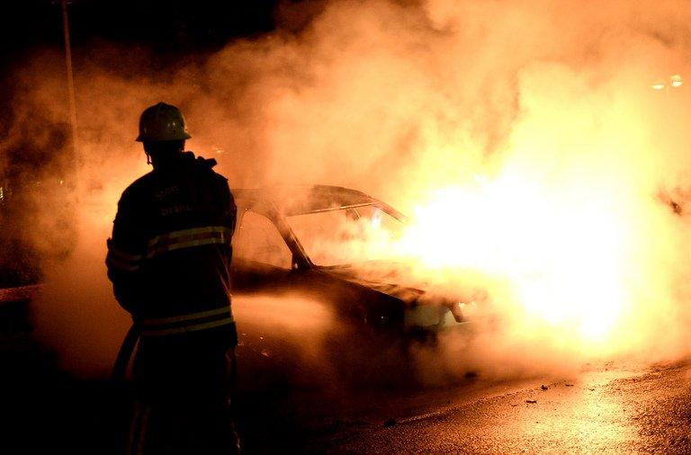Firemen extinguish a burning car in Kista after youths rioted in few differant suburbs around Stockholm, on May 21, 2013