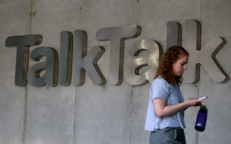 A woman views her phone as she passes a branded logo outside the Talktalk headquarters in London