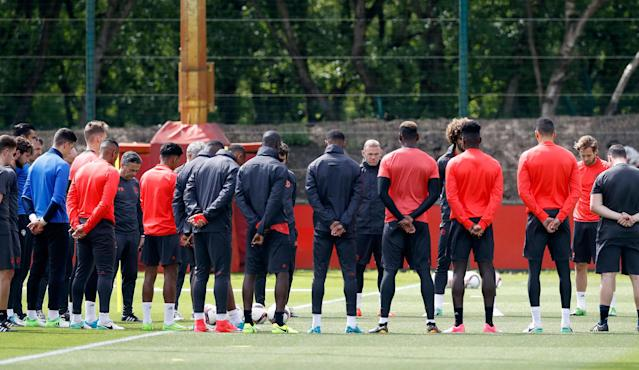 <p>Manchester United's Wayne Rooney, center facing, stands alongside his teammates ahead of a training session at the AON Training Complex in Carrington, England, Tuesday May 23, 2017, for a minute of silence to remember the victims after an apparent suicide bomber attacked an Ariana Grande concert on Monday night. (Martin Rickett/PA via AP) </p>