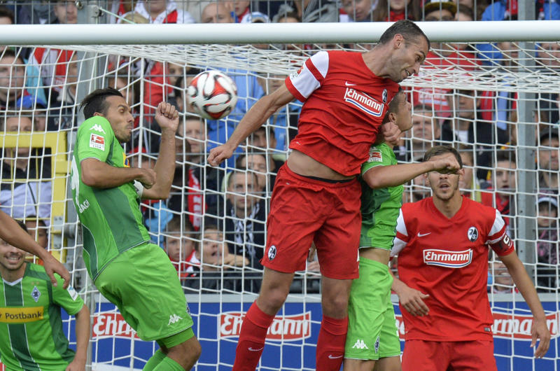 Freiburg's defender Pavel Krmas (C-L) and Moenchengladbach's defender Martin Stranzl (L) vie for the ball on August 31, 2014
