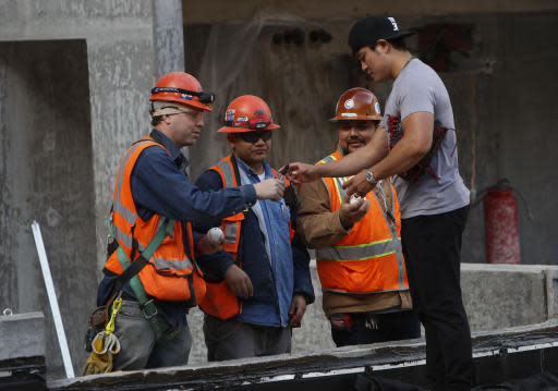Texas Rangers outfielder Shin-Soo Choo of South Korea, right, stops to sign autographs for workers during a tour of the under construction baseball field at the new Texas Rangers stadium in Arlington, Texas, Wednesday, Dec. 4, 2019. (AP Photo/LM Otero)