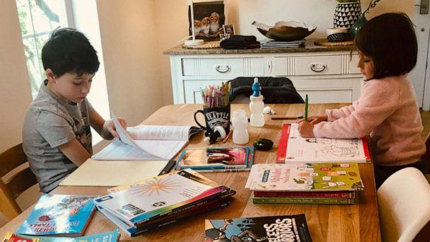 PHOTO: This photo provided by Natasja Billiau, shows her two children, Victor, 8, and Anna Laura, 5, studying at the kitchen table in their Seattle area home Thursday, March 12, 2020, after their school was shut down for weeks due to the coronavirus. (Natasja Billiau via AP)