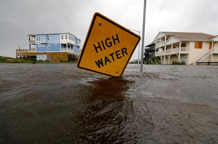 Flood waters lap at a high water warning sign that was partially pushed over by Hurricane Florence on Oak Island, North Carolina, U.S., September 15, 2018. REUTERS/Jonathan Drake