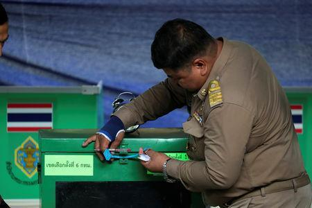 An official seals a ballot box at a polling station, before voting begins in the general election in Bangkok, Thailand, March 24, 2019. REUTERS/Athit Perawongmetha