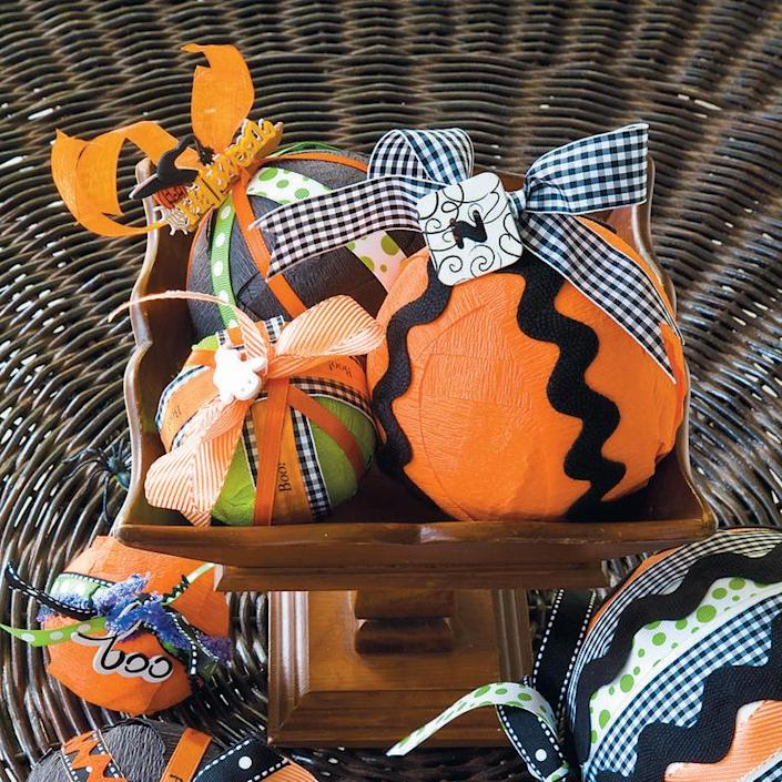 """<p>These charm balls are the cutest centerpieces to honor All Hallows' Eve. You could even do some that are just fall and keep them around well into Thanksgiving. </p><p><em><a href=""""https://www.womansday.com/home/crafts-projects/a28612676/charm-balls/"""" rel=""""nofollow noopener"""" target=""""_blank"""" data-ylk=""""slk:Get the tutorial for Charm Balls."""" class=""""link rapid-noclick-resp"""">Get the tutorial for Charm Balls. </a></em></p>"""