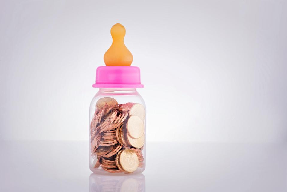 Baby Bottle Filled With Coins Against White Background