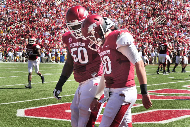 Arkansas quarterback Brandon Allen (10) is accompanied off of the field by teammate Grady Ollison (50) after Allen scored a touchdown in the first half of an NCAA college football game agaisnt Southern Mississippi in Fayetteville, Ark., Saturday, Sept. 14, 2013. Allen left the game with an injury. (AP Photo/April L Brown)