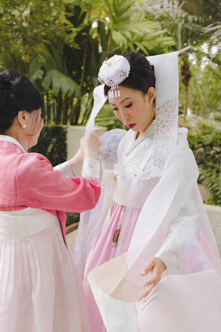 My amazing mother helping me the next day with my <em>daenggi</em>, the traditional cloth ribbon worn by Korean women. She was instrumental in choosing our <em>hanboks</em>.