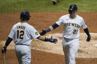 Milwaukee Brewers' Logan Morrison is congratulate by Justin Smoak (12) after hitting a home run during the fourth inning of a baseball game against the Cincinnati Reds Friday, Aug. 7, 2020, in Milwaukee. (AP Photo/Morry Gash)