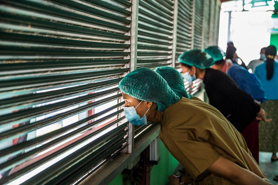 """Health care workers watch protesters demonstrate against Myanmar's military coup in Myanmar's capital of Yangon, Feb. 28.<span class=""""copyright"""">The New York Times</span>"""