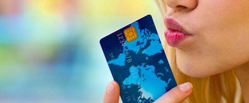 woman holding credit card near to her lips