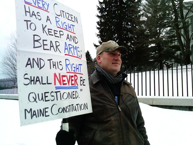 Michael Hein of Augusta, Maine, holds a sign in front of the Maine State house during a Gun Appreciation Day rally, Saturday, Jan. 19, 2013. Rallies are being held by gun rights advocates four days after President Barack Obama unveiled a sweeping plan to curb gun violence. (AP Photo/Glenn Adams )