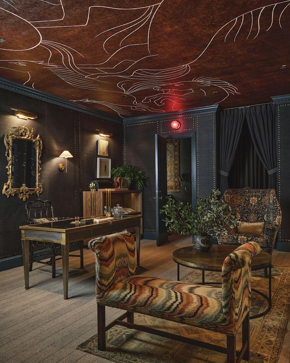 """<p>""""The room is in the basement, which poses a challenge but I'm so excited about what's going on in there and the parameters really force you into the design,"""" says Dallas designer <a href=""""https://www.janetgridley.com/"""" rel=""""nofollow noopener"""" target=""""_blank"""" data-ylk=""""slk:Janet Gridley"""" class=""""link rapid-noclick-resp"""">Janet Gridley</a>. """"I started thinking about atmosphere and how to create a cozy factor in a windowless room, and I don't mean warmth so much as hygge with texture and quiet. This space is very textural, tonal, and moody with lots of soft surfaces."""" </p><p>Gridley found design inspiration from her grandfather's study that she was enchanted by growing up. He was a country doctor and lifelong horseman and his office was filled with books on all kinds of subjects, from beekeeping to medicine and the room's walls were clad in grasscloth. She was also inspired by stories of Preston Hollow in the '30s and '40s as told by an eclectic neighbor when the area was still full of cotton fields and dairy farms and kids rode horses to school. Gridley began weaving together a story for this space and also imagined the closets housing a vinyl room for playing favorite records and a sound booth for hosting podcasts. </p><p>This space is home to a cozy lounge area for reading, studying, or enjoying stimulating conversation with seating upholstered in <a href=""""https://www.wellstextiles.com/"""" rel=""""nofollow noopener"""" target=""""_blank"""" data-ylk=""""slk:Wells Textiles"""" class=""""link rapid-noclick-resp"""">Wells Textiles</a> and <a href=""""https://zoffany.com/"""" rel=""""nofollow noopener"""" target=""""_blank"""" data-ylk=""""slk:Zoffany"""" class=""""link rapid-noclick-resp"""">Zoffany </a>fabrics. A striking horse mural by Area Environments on the ceiling depicts the inspiration from her grandfather and neighbor while Sisal wallpaper from Rifle Paper Co. that's ornamented with more than 250 studs makes the space feel soft, insulated, and restful. Gridley has also filled the room with an abundance of personal"""