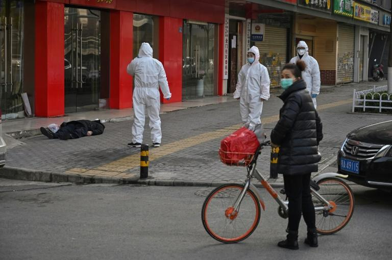 Despite being close to the hospital, the body lay on the ground for more than two hours before being carried away by emergency workers in full hazmat suits