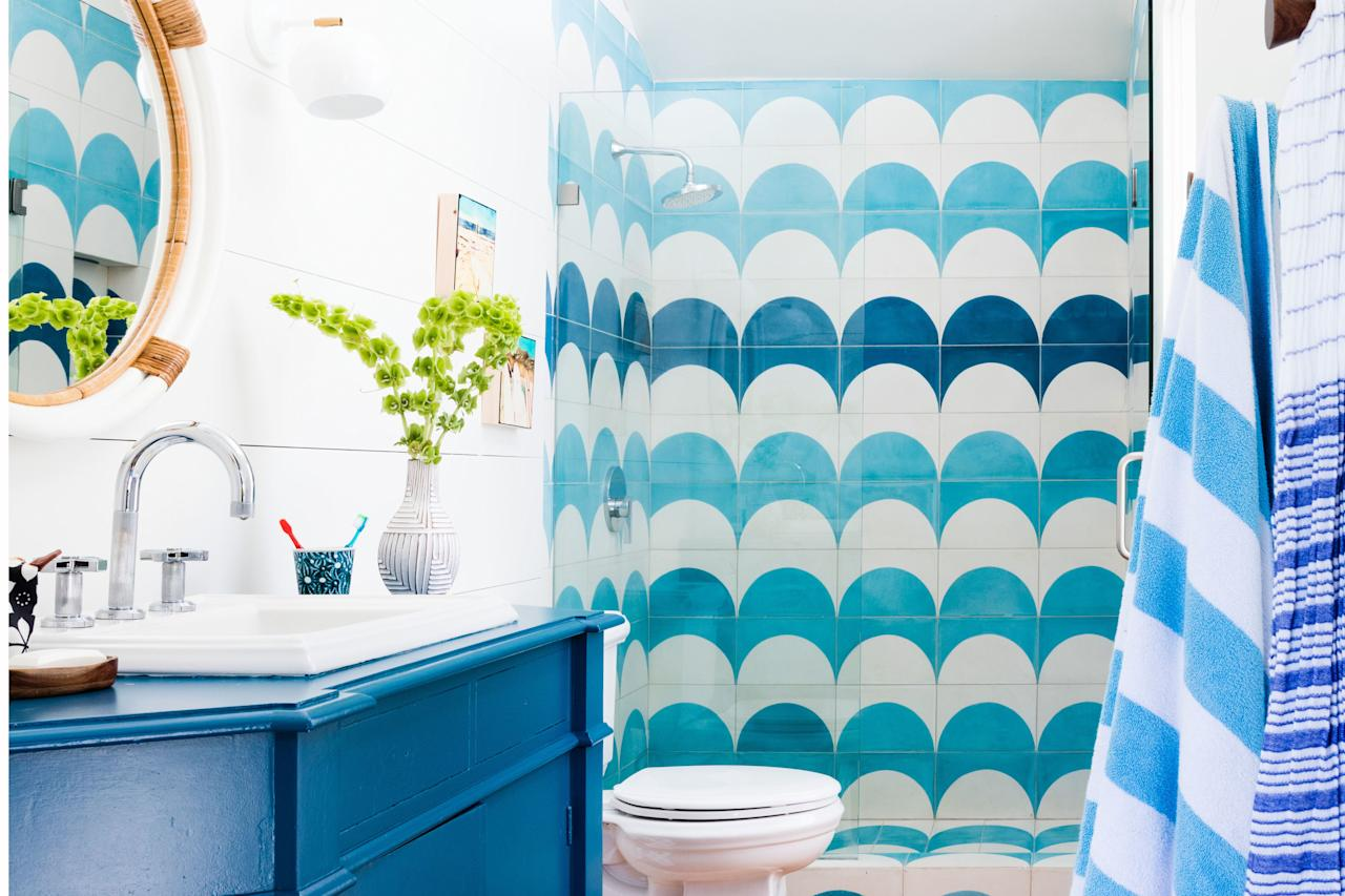 "<p>Cement shower tiles by <a href=""http://pophamdesign.com"">Popham</a><a href=""http://pophamdesign.com"" target=""_blank""> Design</a> mimic ocean waves in this spacious shower. While blue accents throughout the bath complement them, they still remain the star of the show.</p> <ul><li><a href=""https://www.coastalliving.com/homes/decorating/beachy-boho-california-house-tour"" target=""_blank"">Tour the rest of the funky California beach house here.</a></li> </ul><p><strong>Idea Spotlight: </strong>Spruce up existing cabinetry with a fresh coat of paint. Here, designer <a href=""http://www.dehnbloom.com/about/"" target=""_blank"">Allison Bloom</a> used <a href=""https://www.benjaminmoore.com/en-us/color-overview/find-your-color/color/762/pacific-palisades?color=762"" target=""_blank"">Pacific Palisades by Benjamin Moore.</a></p>"