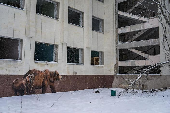 <p>Graffiti daubs a building on the main square in the town of Pripyat (Getty Images) </p>