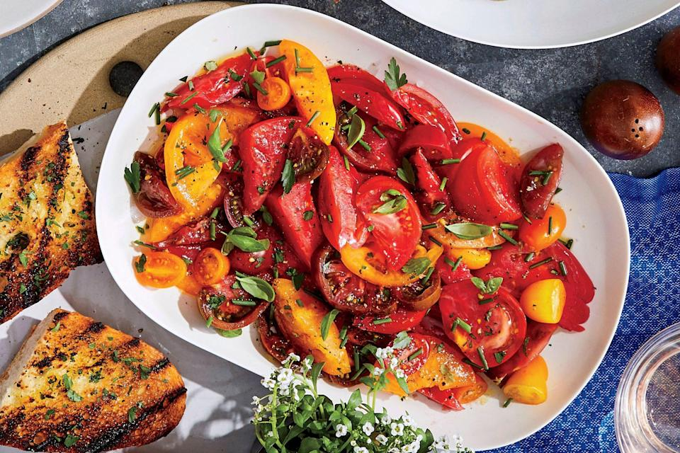 """<p>Make this simple yet memorable <a href=""""https://www.southernliving.com/veggies/tomatoes/summer-tomato-salad"""" rel=""""nofollow noopener"""" target=""""_blank"""" data-ylk=""""slk:tomato salad"""" class=""""link rapid-noclick-resp"""">tomato salad</a> in the height of summer, when tomatoes and fresh herbs abound. It doesn't matter what variety of tomatoes you use, or the type of herbs (choose soft herbs, not woody ones like rosemary or thyme), as long as you mix them up—any combination will look beautiful and taste great. Be sure to let the tomatoes stand for at least 10 minutes, to allow them to marinate in the dressing and fully release their juices into the vinaigrette. Serve the salad at room temperature alongside burgers, grilled chicken, or even a simple piece of fish. It also makes a colorful (and portable!) addition to a <a href=""""https://www.southernliving.com/food/holidays-occasions/summer-party-menus"""" rel=""""nofollow noopener"""" target=""""_blank"""" data-ylk=""""slk:summer potluck"""" class=""""link rapid-noclick-resp"""">summer potluck</a> or cookout. </p>"""