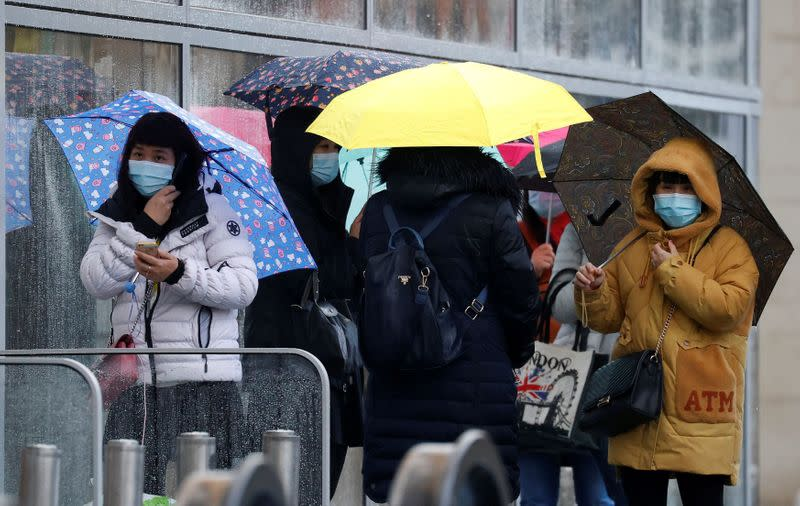 FILE PHOTO: People wearing face masks shelter under umbrellas outside a department store following the outbreak of the coronavirus disease (COVID-19) in Manchester