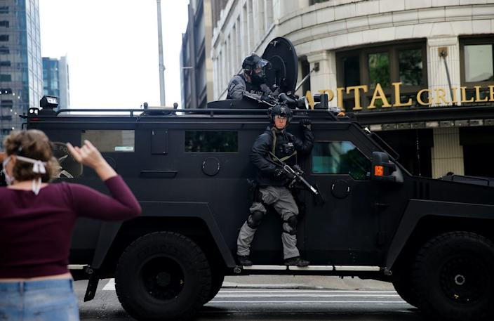 Seattle police drive by protesters in an armored vehicle on May 31, 2020.