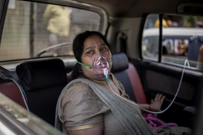 A COVID-19 patient receives oxygen while sitting in a car
