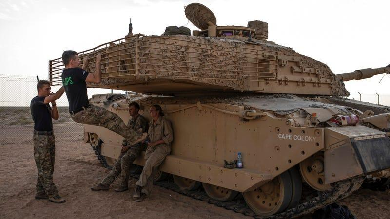 UK soldiers hang out with their tank.