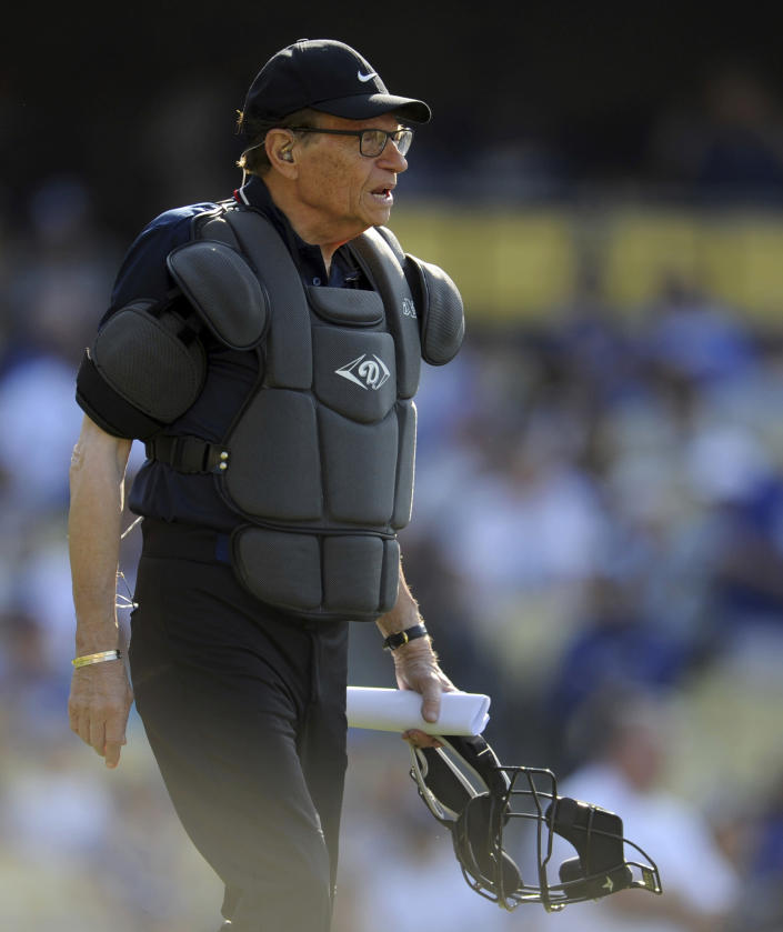 TV host Larry King works as the home plate umpire during the Old-Timers game prior to a baseball game between the Atlanta Braves and the Los Angeles Dodgers Saturday, June 8, 2013, in Los Angeles. King, the suspenders-sporting everyman whose broadcast interviews with world leaders, movie stars and ordinary Joes helped define American conversation for a half-century, died Saturday, Jan. 23, 2021, at age 87. (Keith Birmingham/The Orange County Register/SCNG via AP)