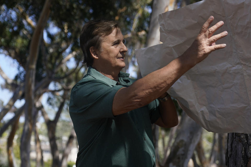 Dan Hirning, founding president of Firezat Inc., reaches for some of the material that protects homes, his company uses as a gust of wind passes, Thursday, Sept. 16, 2021, in Del Mar, Calif. Aluminum wraps designed to protect homes from flames are getting attention as wildfires burn in California. During a fire near Lake Tahoe, some wrapped houses survived while nearby homes were destroyed. (AP Photo/Gregory Bull)