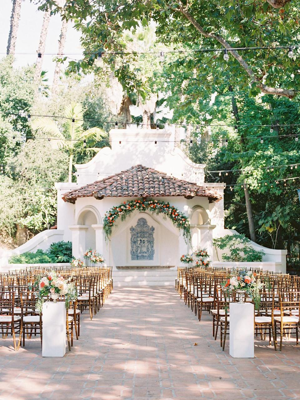 <p>The venue's El Teatro—the open-air theater—served as the site of the duo's vow exchange. A large statement floral installation lined the arch of the altar, which was draped in white silk. Wooden Chiavari chairs defined the space, nodding to the tree canopy overhead; bistro lights offered a romantic touch.</p>