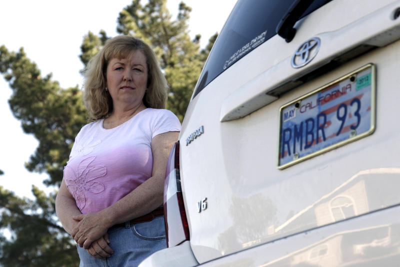 "In this April 21, 2012, photo, Candice Hoglan poses for a portrait with her vehicle with a license plate commemorating the events of Sept. 11, 2001, in Sunnyvale, Calif.  Hoglan's nephew Mark Bingham was one of the passengers of United Airlines Flight 93, which was hijacked by terrorists on Sept. 11. After the 2001 terrorist attacks, California lawmakers sought a way to channel the patriotic fervor and use it to help victims' families and law enforcement.  Their answer: specialty memorial license plates emblazoned with the words, ""We Will Never Forget."" (AP Photo/Marcio Jose Sanchez)"