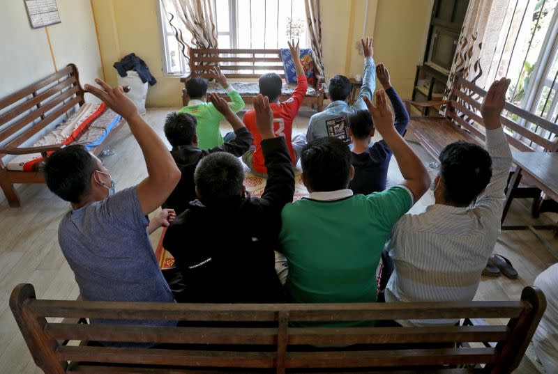 Myanmar nationals including those who said they are police and firemen and recently fled to India flash the three-finger salute at an undisclosed location