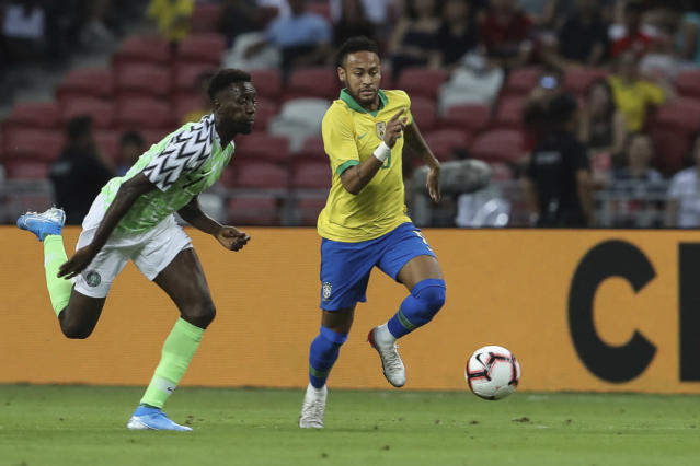 Brazil's Neymar Jr, right, and Nigeria's Anderson Esiti go for the ball during the international friendly match between Brazil and Nigeria in Singapore, Sunday, Oct. 13, 2019. (AP Photo/Danial Hakim)