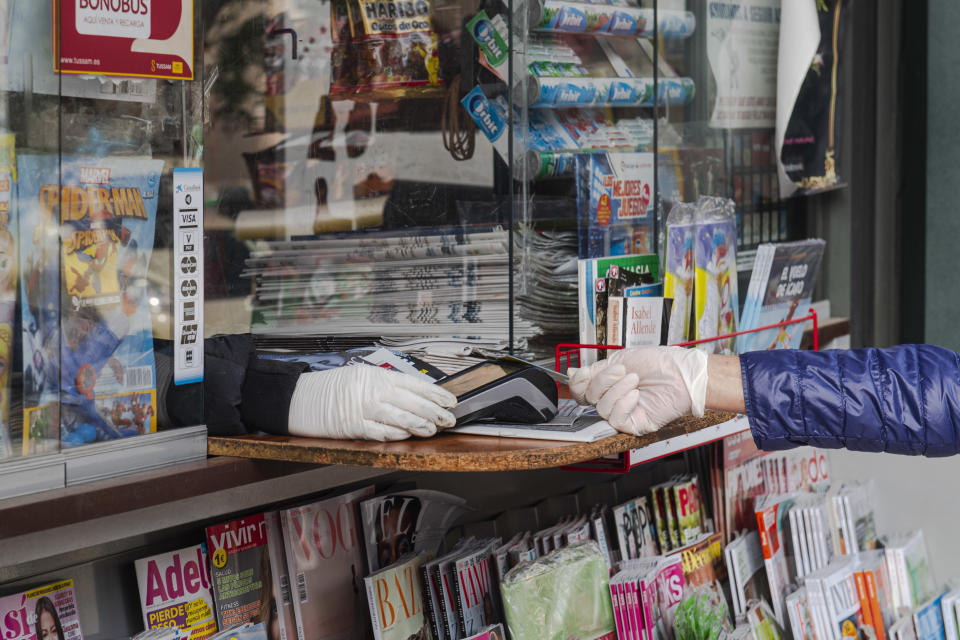 A woman wearing latex gloves pays the newspaper with her credit card in a kiosk on March 29, 2020 in Seville, Spain. (Photo by Niccolo Guasti/Getty Images)