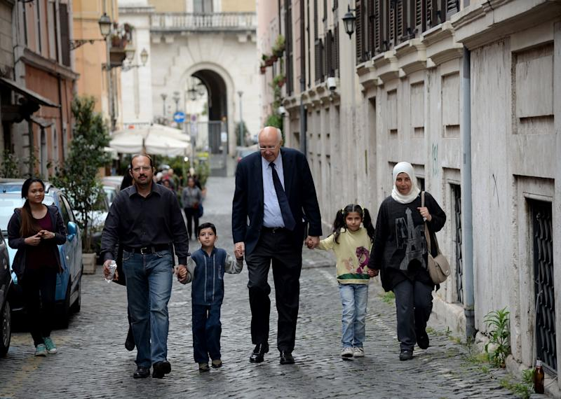 A family of Syrian refugees, part of a group of asylum seekers Pope Francis helped resettle, walks with a member of a Catholic charity on April 18, 2016, in Rome. (Photo: FILIPPO MONTEFORTE via Getty Images)