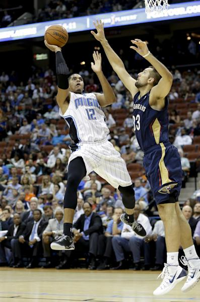Orlando Magic's Tobias Harris (12) shoots over New Orleans Pelicans' Ryan Anderson during the second half of an NBA preseason basketball game in Jacksonville, Fla., Wednesday, Oct. 9, 2013. New Orleans won the game 99-95. (AP Photo/John Raoux)