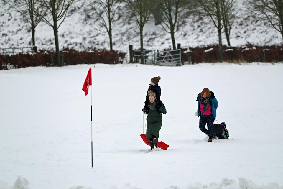 People walk through the snow with sledges on the golf course at Gleneagles in Auchterarder, Perthshire. Heavy snow and freezing rain is set to batter the UK this week, with warnings issued over potential power cuts and travel delays. (Photo by Andrew Milligan/PA Images via Getty Images)