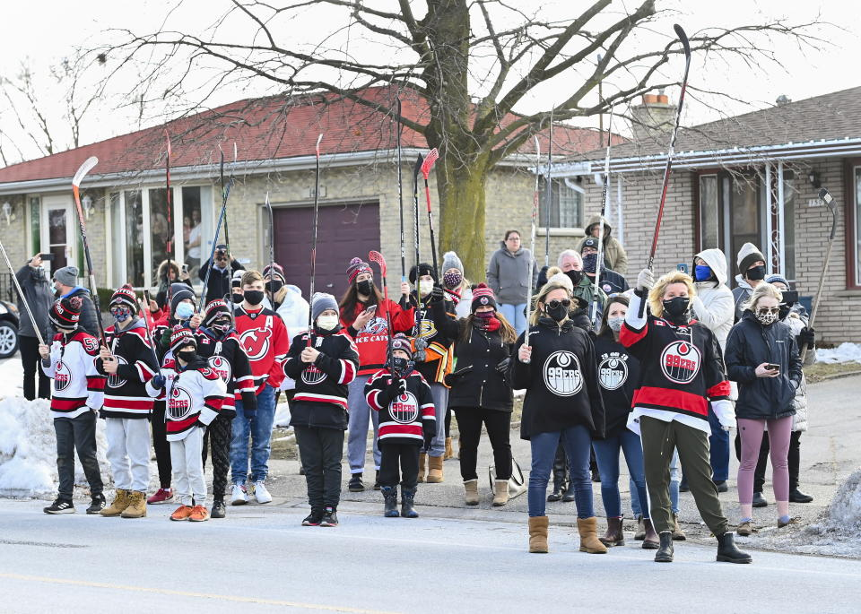 People lift hockey sticks to pay their respects across the street where Walter Gretzky's funeral service was being held in Brantford, Ontario, on Saturday, March 6, 2021. Walter Gretzky also know as Canada's hockey dad was 82 years old. (Nathan Denette/The Canadian Press via AP)