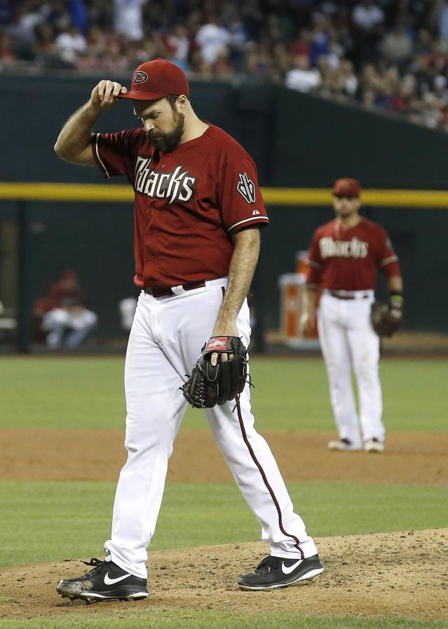 Arizona Diamondbacks' Josh Collmenter, left, walks off the pitcher's mound with his head down after giving up a 2-run home run to Los Angeles Dodgers' Adrian Gonzalez as Diamondbacks' Martin Prado, right, looks on during the third inning of a baseball game on Sunday, May 18, 2014, in Phoenix. (AP Photo/Ross D. Franklin)