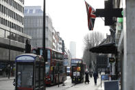 A coronavirus information sign is displayed by a bus stop with a Union flag above in London, Friday, Jan. 15, 2021, during England's third national lockdown since the coronavirus outbreak began. The U.K. is under an indefinite national lockdown to curb the spread of the new variant, with nonessential shops, gyms and hairdressers closed, most people working from home and schools largely offering remote learning. (AP Photo/Matt Dunham)