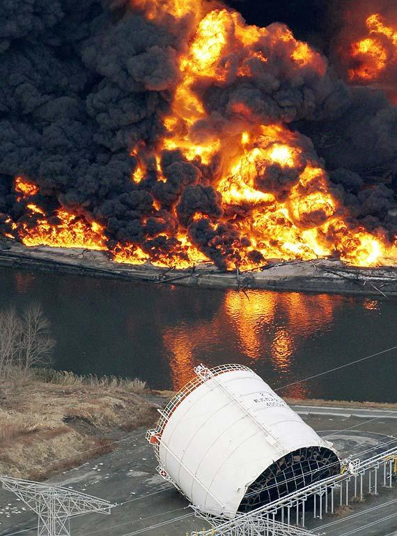 Gas storage facilities burn in Tagajo, Miyagi Prefecture, Saturday morning, March 12, 2011 after Japan's biggest recorded earthquake slammed into its eastern coast Friday. (AP Photo/Kyodo News)